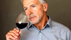 stock-footage-closeup-of-senior-man-drinking-red-wine-against-dark-background
